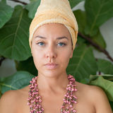 Portrait of a young woman in a turban and with beads Stock Photos