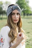 Portrait of young woman with turban on head and posing outdoor royalty free stock photos
