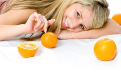Portrait of young woman with two orange. Closeup portrait of happy young woman with two orange laying on a floor Stock Photography