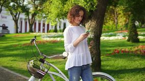 Portrait of a young woman typing a message using her smartphone standing in the city park near her city bicycle with. Flowers in its basket and drinking green stock video