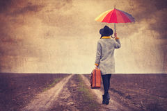 Portrait of a young woman with umbrella and suitcase Royalty Free Stock Photos