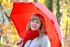 Portrait of the young woman under a red umbrella in the autumn park.  Royalty Free Stock Photography