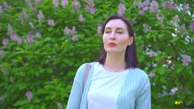 Portrait of a young woman using allergic nose spray on the background of flowering plants in the Park. Close up stock video footage