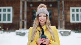 Portrait of young woman using app on smartphone, smiling and texting on mobile phone. Woman Wearing A Winter Coat Near a stock video