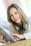 Portrait of young woman using headphones and tablet Stock Photography