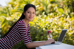 Portrait of young woman using laptop at restaurant Stock Photo