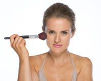 Portrait of young woman using makeup brush Stock Images