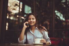 Portrait of Young Woman Using Mobile Phone in Cafe Stock Photos