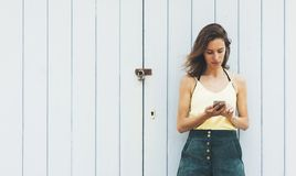 Portrait young women using smart phone isolated on background vintage wooden boards wall background mock up, pretty hipster female stock photography