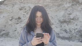 Portrait of young woman using smartphone outdoor. The wind easily waves her hair. Portrait of cute brunette woman using smartphone outdoor on the street stock video
