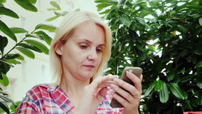 Portrait of a young woman using a smartphone on a summer terrace in a cafe. Tourism in Europe - the city of Graz in. Young woman is using the phone in a cafe stock video