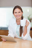 Portrait of a young woman using a tablet computer while drinking Stock Photos