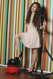 Portrait of young woman with vacuum cleaner standing against colorful striped wall Stock Images