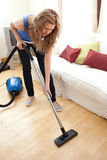 Portrait of a young woman vacuuming. At home Stock Photos