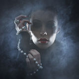 Portrait of a young woman in a vampire dress. Portrait of a young and attractive brunette Caucasian woman posing in a vampire dress and jewlery. The image is Stock Images