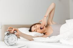 Portrait of young woman waking up in bed with white linen, yawning and touching ringing alarm clock stock photos