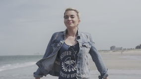 Portrait of young woman walking on beach with arms outspread and face raised in sky enjoying peace. Happy young woman in denim jacket relaxing on lonely beach stock video