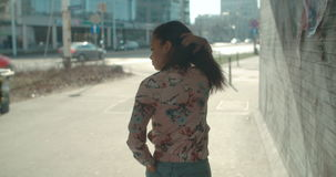Portrait of a young woman walking in the city streets. stock footage