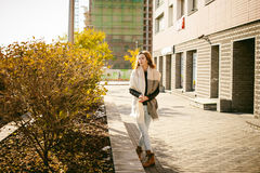Portrait of young woman walking outdoors on warm autumn afternoon Stock Photo