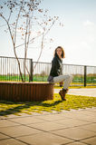 Portrait of young woman walking outdoors on warm autumn afternoon Stock Image
