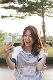 Portrait of young woman watching to mobile phone screen with sur Stock Image