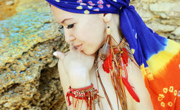 Portrait of a young woman wearing boho chic headband and handmade feathers necklace and earrings. Against stone backdrop Royalty Free Stock Photo