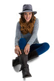 Portrait of young woman wearing boots. While sitting against white background Royalty Free Stock Image