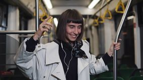 Portrait of young woman wearing in coat with headphones listening to music and funny dancing in public transport. He stock video
