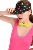 Portrait of a young woman wearing a colorful polka dotted hat and a neon green bowtie. Royalty Free Stock Photo