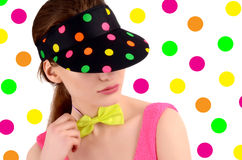 Portrait of a young woman wearing a colorful polka dotted hat and a neon green bowtie. Stock Photos