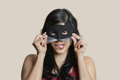Portrait of a young woman wearing eye mask while biting lip over colored background Stock Images