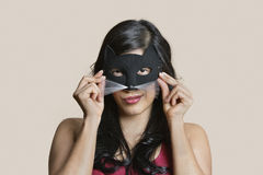 Portrait of a young woman wearing eye mask over colored background Royalty Free Stock Image