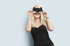 Portrait of a young woman wearing eye mask over light blue background Royalty Free Stock Photo
