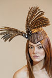 Portrait of a young woman wearing feathered headdress on colored background Stock Photography