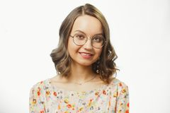 Portrait of young woman wearing floral blouse, round eyeglasses for vision, has light brown hair up to shoulders, with. Sincere look and charming smile. Concept royalty free stock photos