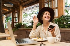 Portrait of young woman wearing hat using smartphone and earphones royalty free stock photo