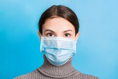 Portrait of young woman wearing medical mask at blue background. Protect your health. concept