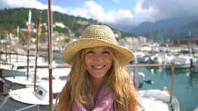 Portrait of young woman wearing straw hat smiling at the camera with seacoast background. stock footage