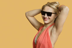 Portrait of a young woman wearing sunglasses with hands in hair over colored background Royalty Free Stock Image