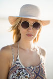 Portrait of young woman wearing sunglasses and hat at beach. During sunny day Stock Photos