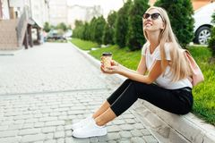 Portrait of a young woman wearing sunglasses outdoors with coffee. Girl sitting on the lawn and drinking coffee. royalty free stock photography