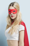 Portrait of young woman wearing superhero costume against blue background Royalty Free Stock Photos
