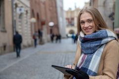 Blonde beautiful woman holding tablet on city street. royalty free stock image