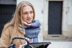 Blonde beautiful woman holding tablet on city street. stock image
