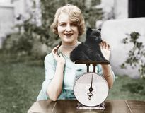 Portrait of a young woman weighing her puppy on a weighing scale royalty free stock images