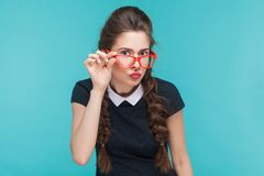 Portrait of young woman with wevy pigtails and red glasses royalty free stock images