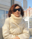 Portrait of a young woman in a white coat and sun glasses Stock Photos