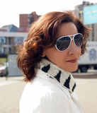 Portrait of a young woman in a white coat and sun glasses Royalty Free Stock Photo