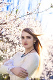 Portrait of young woman in white dress in spring flowers. In the garden Stock Photo
