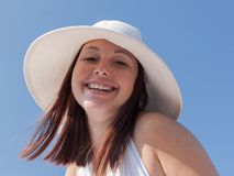 Portrait of young woman in white hat against clear sky. Girl in white broad-brim hat looking at camera laughing, low angle view stock photography
